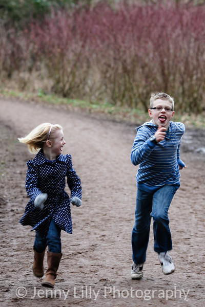 bother and sister running  in woods