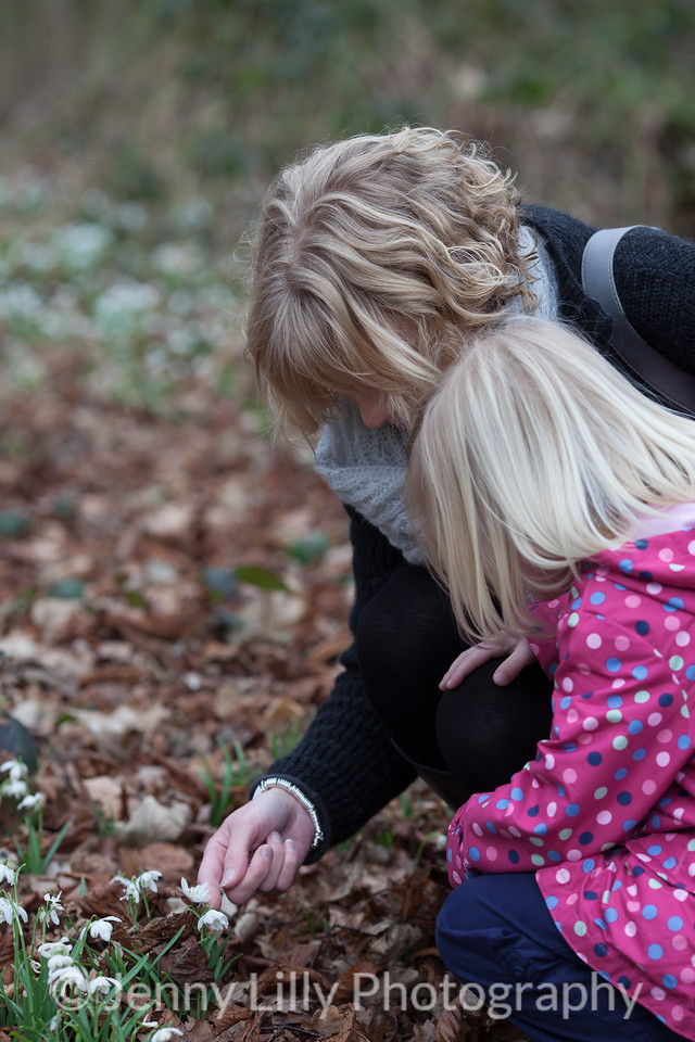 pretty woman and child in woods of snowdrops