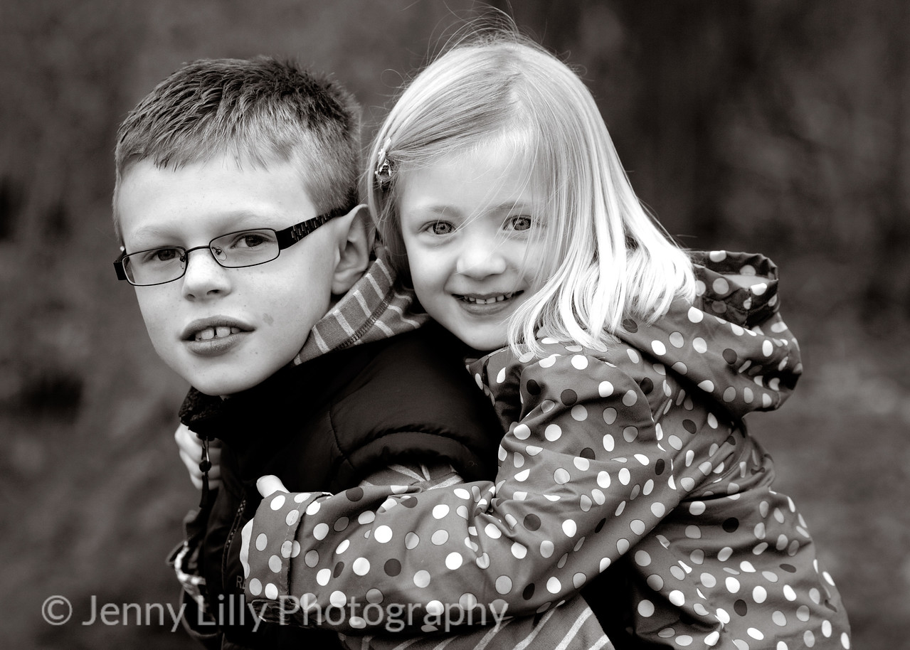 pretty child having a piggy back on her brother's back in black and white