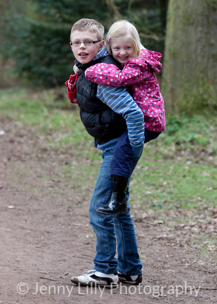 pretty girl having a piggy back on her brother's back  in woods
