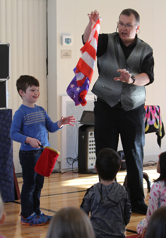 . Celebration of Roudenbush Community Center reopening after renovations. Trevor Welt, 4, of Acton, helps magician Dave Anderson of Newton, N.H., who turned red, white and blue handkerchiefs into a flag. (SUN Julia Malakie)