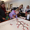 Celebration of Roudenbush Community Center reopening after renovations. Missy Casserly of Westford watches her daughter Addison, 4, add her thumbprint to the thumbprint tree, which was the idea of Roudenbush board member Mary Yao of Westford, right. At center is board co-chair Leanna Moran of Westford. (SUN Julia Malakie)