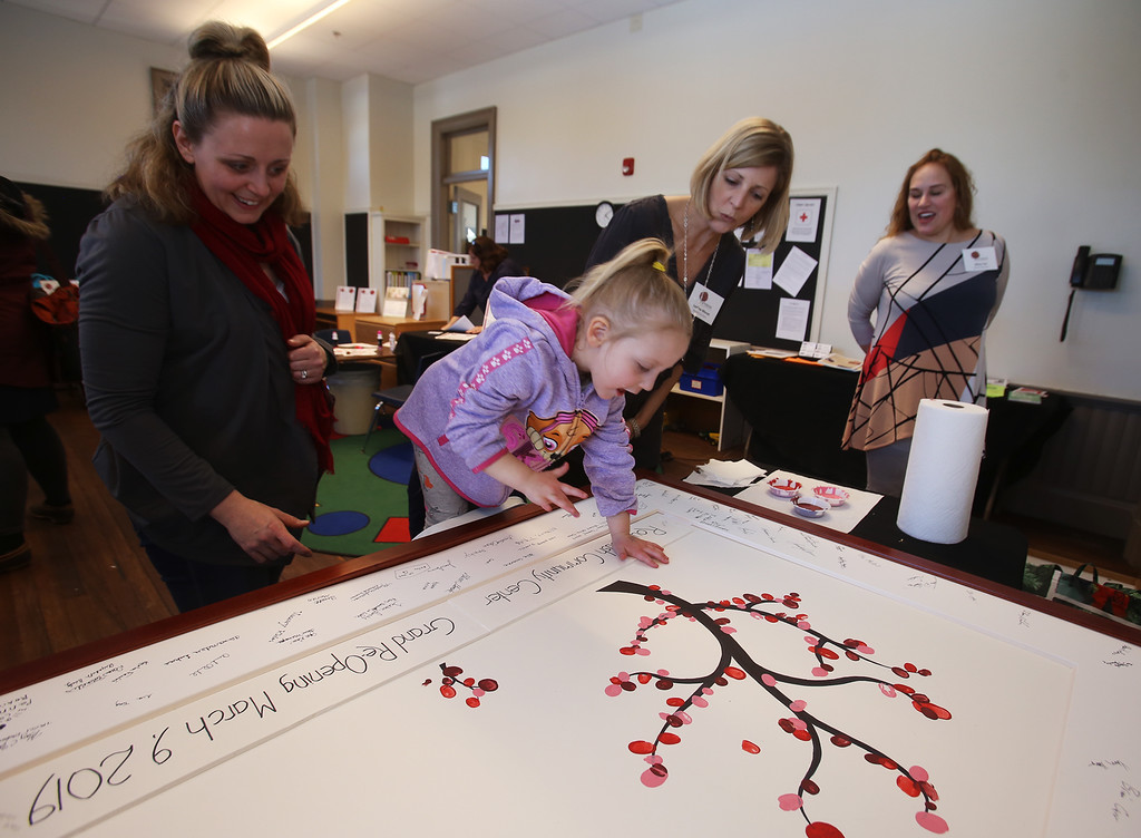 . Celebration of Roudenbush Community Center reopening after renovations. Missy Casserly of Westford watches her daughter Addison, 4, add her thumbprint to the thumbprint tree, which was the idea of Roudenbush board member Mary Yao of Westford, right. At center is board co-chair Leanna Moran of Westford. (SUN Julia Malakie)