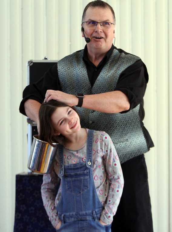 . Celebration of Roudenbush Community Center reopening after renovations. Magician Dave Anderson of Newton, N.H., finds coins behind the ears of Ella Cohen, 8, of Westford. (SUN Julia Malakie)