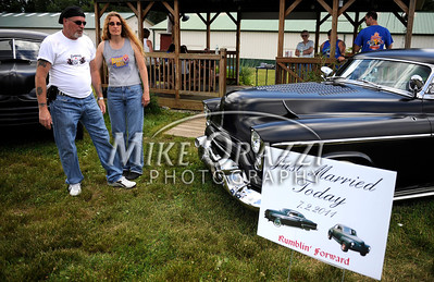 7/2/2011 Mike Orazzi | Staff Frank and Connie Perna stand between their 47 Ford and 53 Olds classic cars during the Rumblers Nomads car show at the Terryville Fair Grounds on Saturday, July 2, 2011. The Pernas got married at the show on Saturday morning.