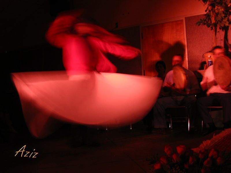 Whirling dervish Aziz Abbatiello with off-stage musicians [text]
