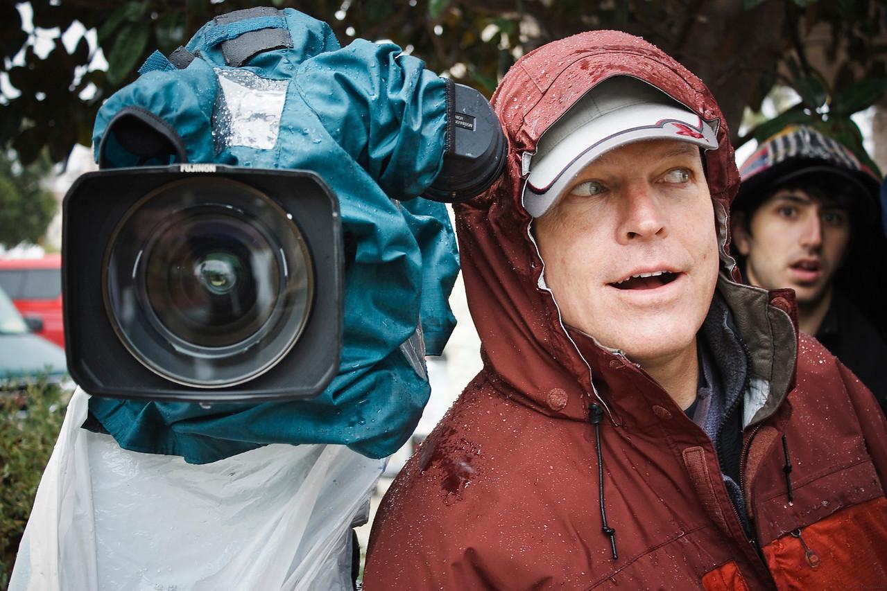 Mike (Cameraman) and Adam (Cameraman) set up the Panasonic HD camera with rain gear.