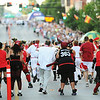 Globe/T. Rob Brown<br /> On their way: Participants are chased by inflatable-club-wielding members of the MO-KAN Roller Girlz Thursday evening, July 19, 2012, during the downtown Joplin event on Main Street.