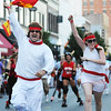 "Globe/T. Rob Brown<br /> Two participants of the Running of the Bulls event try to stir up the ""bulls"" as they are chased by inflatable-club-wielding members of the MO-KAN Roller Girlz Thursday evening, July 19, 2012, during the downtown Joplin event on Main Street."