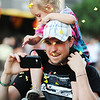 Globe/T. Rob Brown<br /> Confetti experience: From the crowd, Josh Bogard, of Joplin, uses his phone to record video of the Running of the Bulls event as he holds a friend's niece, Brooklinn Felton, 4, of Joplin, on his shoulders so she can get a better look, though she is distracted by falling confetti, Thursday evening, July 19, 2012, during the downtown Joplin event on Main Street.