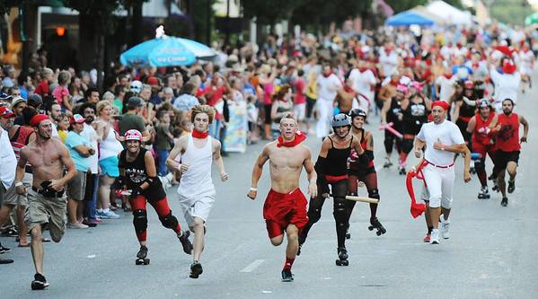 Globe/T. Rob Brown<br /> The heat is on: The race leaders of the Running of the Bulls event are chased by inflatable-club-wielding members of the MO-KAN Roller Girlz Thursday evening, July 19, 2012, during the downtown Joplin event on Main Street.
