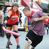 Globe/T. Rob Brown<br /> A member of the MO-KAN Roller Girlz swings at a Running of the Bulls participant Thursday evening, July 19, 2012, during the downtown Joplin event on Main Street.