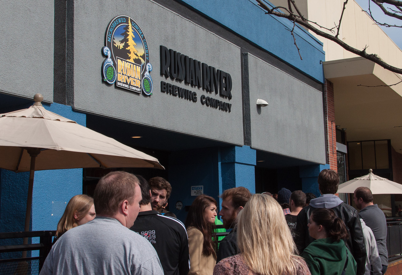 A crowd gathers in front of the Russian River Brewing Company shortly before they open.