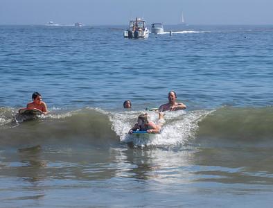 Dad teaching daughter to boogie board on gentle waves