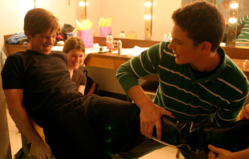 left to right : senior Jake Humphrey, junior Jessie Hager, sophomore Nathan Bartlett. Nathan struggles to pull off Jake's boot in a dressing room used for preparation for Aida.