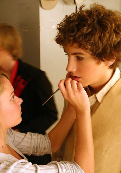 junior Hannah Croisant applies make-up to junior John Diedrich in a dressing room for aida.