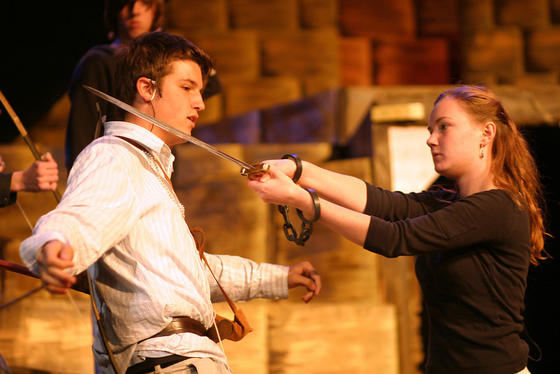 junior Sarah Casey holds a sword to junior Skye Theonnes' neck during Aida rehearsal.