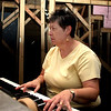 orhcestra teacher Karen McGhee-Hensel plays piano backstage for Aida.