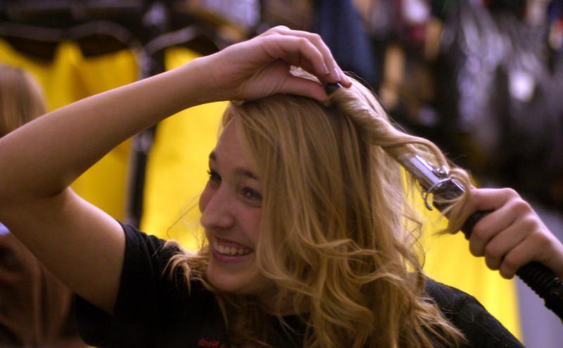 junior Danielle Killingsworth curls her hair backstage for the play aida.
