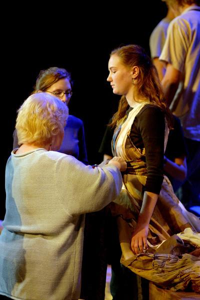 drama teacher Maureen Davis fixes junior Sarah Casey's costume during Aida rehearsal.
