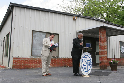 Against the backdrop of the new West End Family Support Center, Archbishop Wilton D. Gregory, holding the microphone, leads a responsive prayer with the building dedication participants. Standing with him is Jim Verrecchia, director of support programs for the Society of St. Vincent de Paul Atlanta.