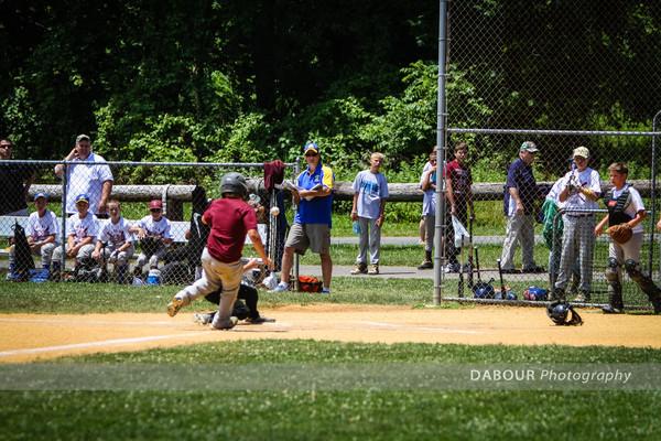 A member of the Garnet All Star baseball team slides into home plate.