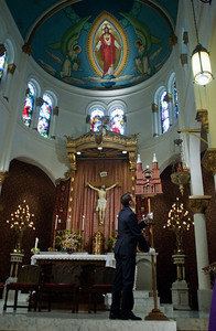 David Castronovo puts the tintinnabulum in its rightful place on the altar. The tintinnabulum, a bell on a pole, signifies the church's link with the Pope. It's one of two symbols on display at a basilica. The other is the ombrellino, an elaborate umbrella always displayed halfway open to signify the church is ready to welcome the Holy Father. (Photo by Thomas Spink)         (Page 2, September 2, 2010 issue)