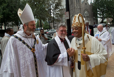 Monastery of the Holy Spirit Abbot, Francis Michael Stiteler, left, and Archbishop Wilton D. Gregory, right, offer words of congratulation to basilica rector Father T. J. Meehan following the Mass of Elevation.  (Photo by Thomas Spink)  (Page 3, September 2, 2010 issue)
