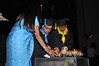 Graduating students light candles with a little help from the teachers
