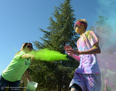 Oroville Hospital environmentalist Debbie McKibben throws colored powder onto a runner as people celebrate fish Saturday, Sept. 24, 2016, during the Salmon Festival in Oroville, California. (Dan Reidel -- Enterprise-Record)