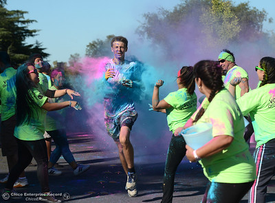 Justin Hickman, 16, a Las Plumas cross country runner, is pelted with colored powder as he comes in third place in the Oroville Hospital 3K Color Dash as people celebrate fish Saturday, Sept. 24, 2016, during the Salmon Festival in Oroville, California. (Dan Reidel -- Enterprise-Record)
