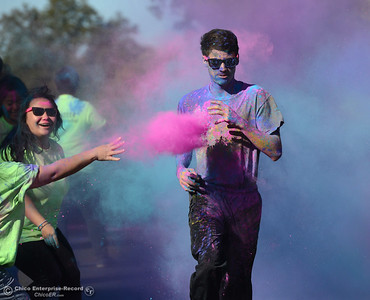 Eiljah Valderrama, 18, a Las Plumas cross country runner, is pelted with colored powder as he comes in second place in the Oroville Hospital 3K Color Dash as people celebrate fish Saturday, Sept. 24, 2016, during the Salmon Festival in Oroville, California. (Dan Reidel -- Enterprise-Record)