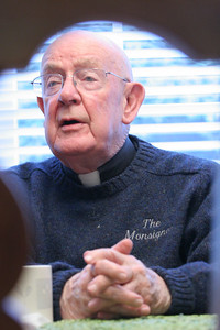 Msgr. R. Donald Kiernan sits in the All Saints Church rectory kitchen, where he enjoys his morning cup of coffee and a bowl of oatmeal.