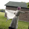 Record-Eagle/Lisa Perkins<br /> Darica Isenhart uses wooden clothespins to hang laundry on the line outside the Samels brothers' farmhouse.