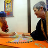 Lama Karma Namgyel, left, and Rev. Carol O'Dowd, scrap up the sand from the mandala so it can be dispersed in a stream at Kanemoto Park.<br /> Members of the  Longmont Buddhist Temple and Drukpa Mila Center dismantled the Buddha of Compassion Sand Mandala and dispersed it at Kanemoto Park in Longmont.<br /> Cliff Grassmick / September 20, 2009