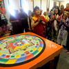 Lama Karma Namgyel, center, prepares to dismantle the sand mandala on Sunday.<br /> Members of the  Longmont Buddhist Temple and Drukpa Mila Center dismantled the Buddha of Compassion Sand Mandala and dispersed it at Kanemoto Park in Longmont.<br /> Cliff Grassmick / September 20, 2009