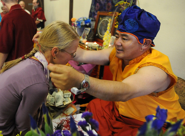 Lama Karma Namgyel, right, puts a blessed string around Heidi Nordlund during the ceremony on Sunday.<br /> Members of the  Longmont Buddhist Temple and Drukpa Mila Center dismantled the Buddha of Compassion Sand Mandala and dispersed it at Kanemoto Park in Longmont.<br /> Cliff Grassmick / September 20, 2009