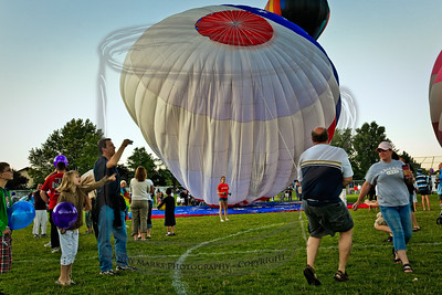 The balloon top is rising, the owner is running, as slow as he can. The girl in orange jumped on the rope but didn't slow the assent.