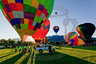 The sun is breaking over the Wasatch as many of the balloons are up or about ready to lift off.