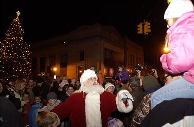 Record-Eagle/Garret Leiva<br /> Santa Claus makes his way through a swarming crowd gathered for his arrival Friday evening in Traverse City. After coming to town on a horse-drawn sleigh, Santa received a key to the city from Traverse City Mayor Pro-Tem, Chris Bzdok. Hundreds turned out to watch the jolly old elf light the 30-foot Douglas fir donated from the Northwestern Michigan College University Center campus.