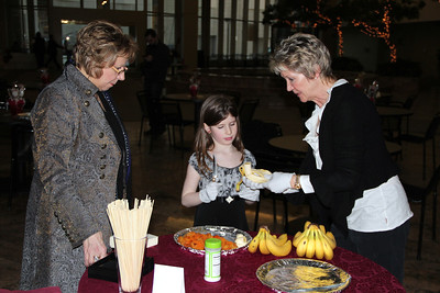 Terri showing Riely how to fix up a banana to be dipped in chocolate while Gloria watches on.