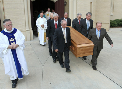 Marist provincial Father Timothy Keating, far left, follows the pallbearers as they process out of church to the funeral hearse.