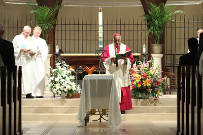 Archbishop Wilton D. Gregory leads the prayer during the final commendation. Following along on the altar are Our Lady of the Assumption deacons Bill Bevacqua, left, and William O'Donoghue.