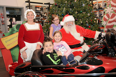 "Emily (11), Travis (9) and little sister Abby (6) have their photo taken with Santa and Mrs. Claus at Schaeffer's Harley-Davidson's annual ""Pictures with Santa"" event. Hamburg, PA"