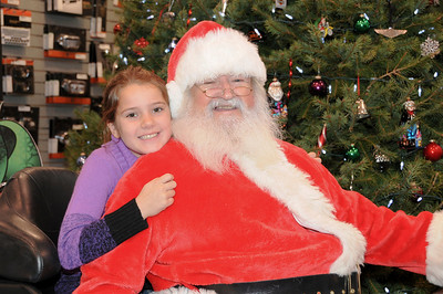 """Isabelle Zawacki, 9, cuddles up to Santa on the back of a Harley-Davidson at Schaeffer's Harley-Davidson's annual """"Pictures with Santa"""" event.  Ashland, PA"""