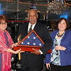 Honoree Dr. Webster Trammell, Vice President of Government and Community Relations and Dr. Maureen Murphy, President Brookdale Community College are presented with a flag from Kristin Michaels of Winning Strategies.