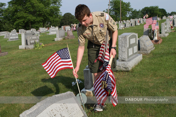 Boy Scout Sam Young, 14 from Pohatcong Township puts out a US flag on a grave site.