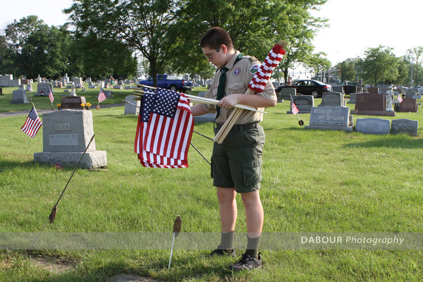 Boy Scout Sean Merkel, 12 from Bloomsbury puts out a US flag on a grave site.