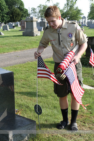 Boy Scout Christian Zurine, 16 from Pohatcong Township puts out a US flag on a grave site.
