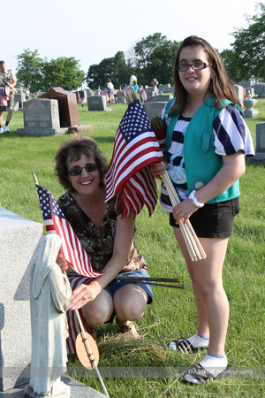 Girl Scout Rose Pettineilli, 11 and Rose Pettineilli both from Alpha puts out a US flag on a grave site.